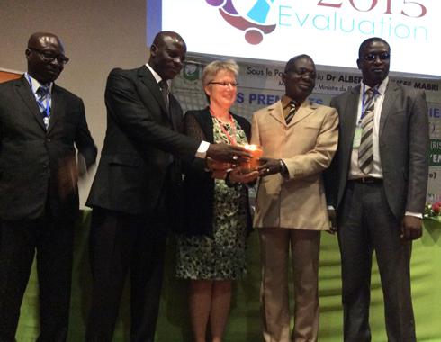 Reception de la flamme de l'année internationale de l'Evaluation en CI des main de Marie Gervais